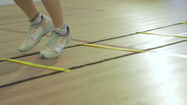 young asian chinese teenage girl athlete legs moving zigzag stepping warm up exercise before playing squash