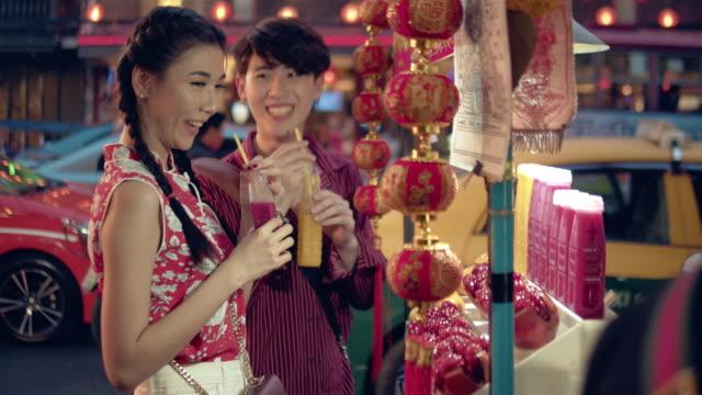 young asian couple having buy juice water. - mercato frutta donna video stock e b–roll