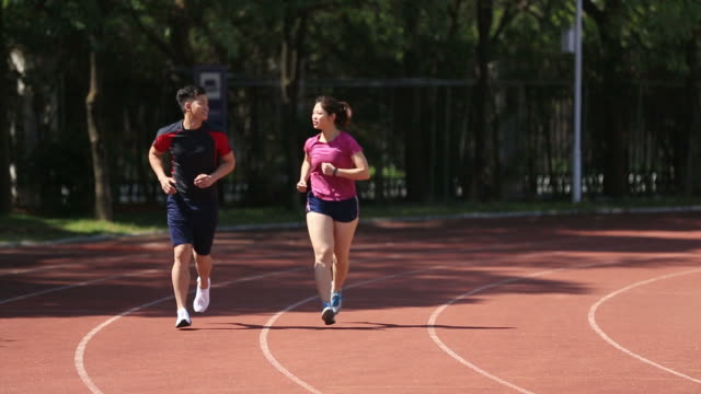 young asian couple jogging in stadium video