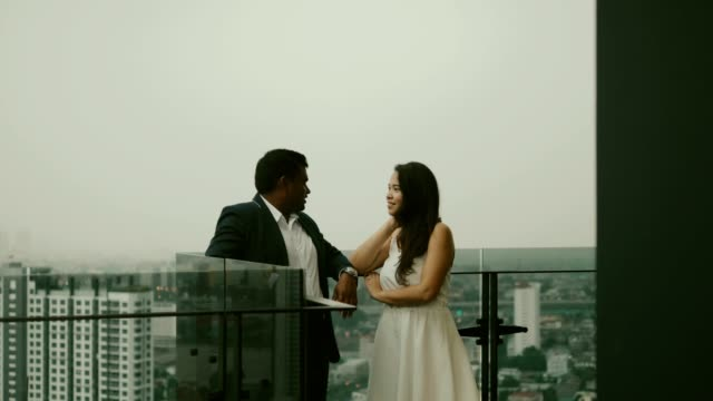 Young Asian couple on the balcony with city scape view- Stock video