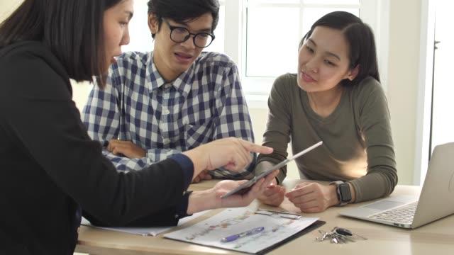 vídeos y material grabado en eventos de stock de pareja joven asiática planificación reunión de hipoteca con el agente de bienes raíces - asia
