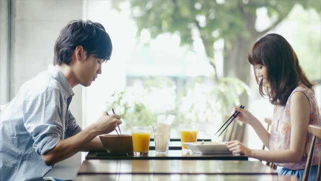若いアジアカップルのテイスティングのお食事には、レストラン「箸 - 対面点の映像素材/bロール
