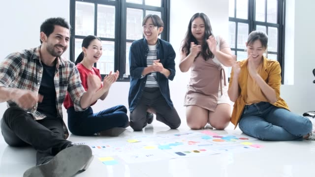 young asian creative diverse group meeting and looking at project plan lay out on floor discuss or brainstorm business strategy Team discussing roadmap to product launch strategy plan con