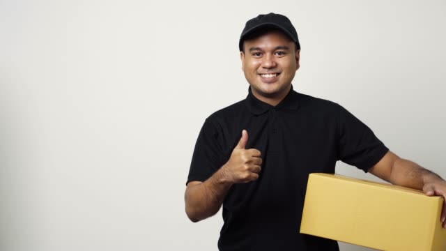 Young asian delivery man in black uniform holding the parcel cardboard pointing the finger to blank space for text on isolated white background. 4k Resolution.
