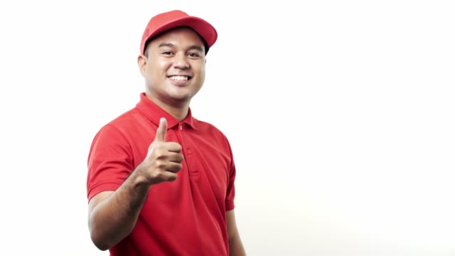 Young asian delivery man in red uniform the parcel cardboard to customer on isolated white background. 4k Resolution.