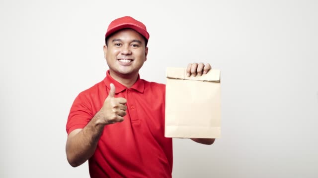 Young asian delivery man in red uniform the parcel paper bag to customer and showing thumbs up on isolated white background. 4k Resolution.