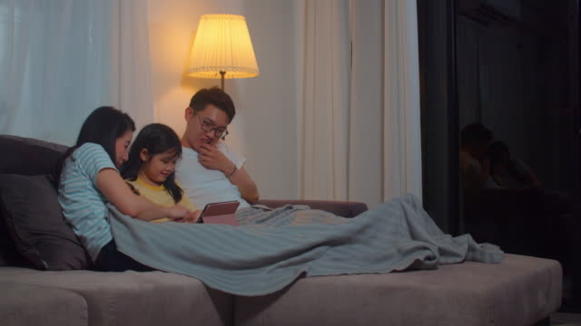 Young Asian family and daughter happy using tablet at home. Japanese mother, father relax with little girl watching movie lying on sofa before going to sleep in living room at house in night.