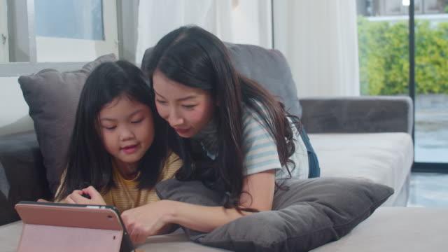 giovane famiglia asiatica e figlia felice di usare il tablet a casa. la madre giapponese si rilassa con la bambina che guarda il film sdraiata sul divano nel soggiorno di casa. mamma divertente e bambino adorabile si stanno divertendo. - corea video stock e b–roll