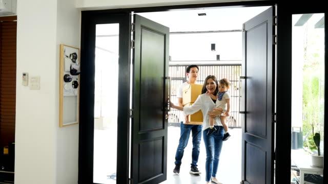 Jeune asiatique famille transportant des boîtes dans nouvelle maison le jour du déménagement - Vidéo