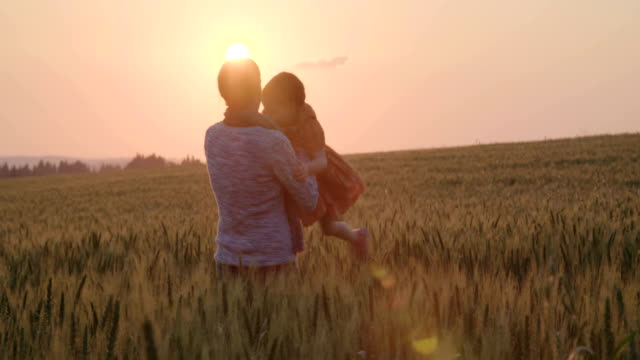 young Asian family in a field with a baby 1 year on hand, the concept of family happiness, beautiful sunlight, sunset, slow motion video