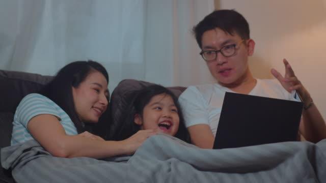 若いアジアの家族は家で娘におとぎ話を読みました。幸せな日本の母親、お父さんは小さな女の子とリラックスして、夜に家で寝室に寝る前にベッドに横たわって良い品質の時間を楽しみま� - 家族 日本人点の映像素材/bロール