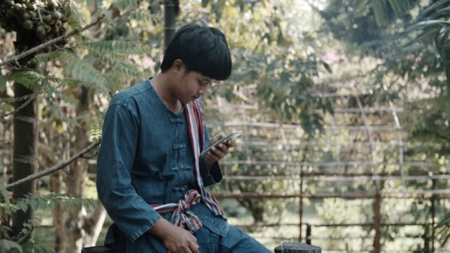 Young asian farmer using cell phone