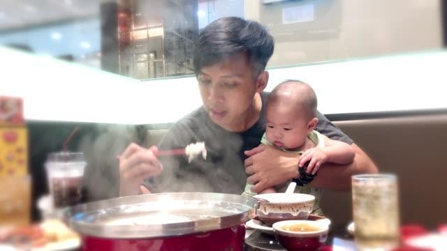 ung asiatisk pappa håller liten pojke medan du äter i restaurangen. - working from home bildbanksvideor och videomaterial från bakom kulisserna