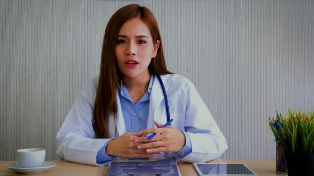młoda azjatycka kobieta lekarz mówi i szuka kamery w wideokonferencji - video filmów i materiałów b-roll