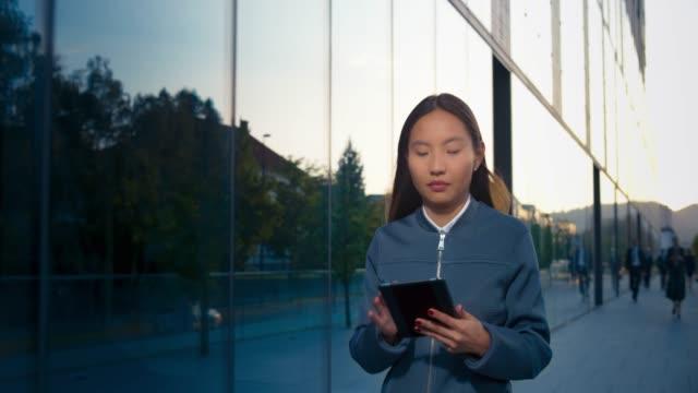 stockvideo's en b-roll-footage met ts jonge aziatische vrouwelijke ondernemer werken aan de digitale tablet tijdens het wandelen langs de moderne business building - mid volwassen vrouw