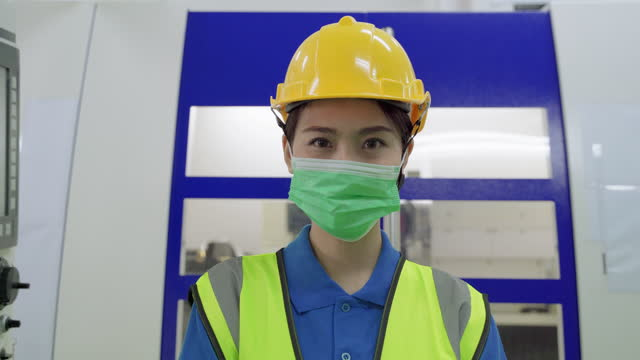 Young Asian female foreman wearing a face mask to prevent COVID 19 infection