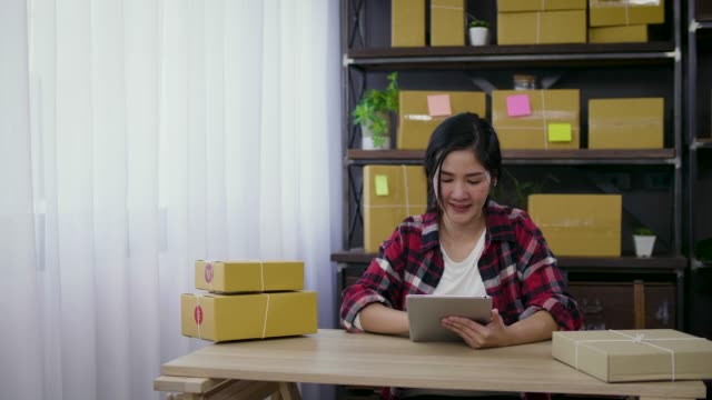 young asian female freelancer using her digital tablet and working at home, small business female owner or start up small business entrepreneur working online marketing packaging box delivery - электронная коммерция стоковые видео и кадры b-roll