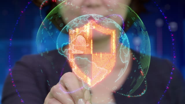 Young Asian female touches futuristic holographic interface and activates shield icon Animation of young Asian female touching futuristic holographic interface to activate software or hardware firewall symbol shield stock videos & royalty-free footage