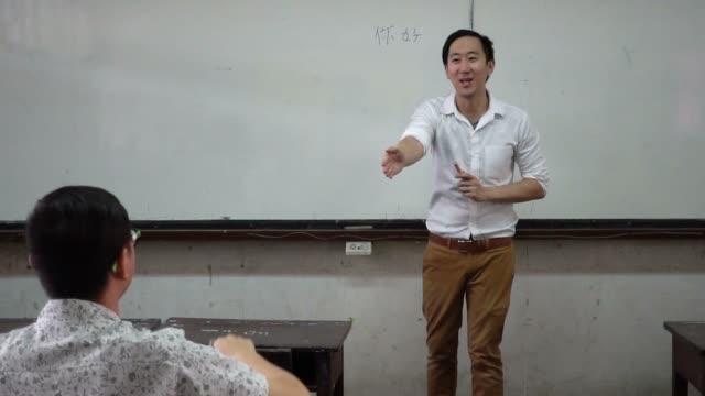 Instructeur de jeunes asiatiques étrangers orientaux langue donnant une leçon de langage en classe - Vidéo