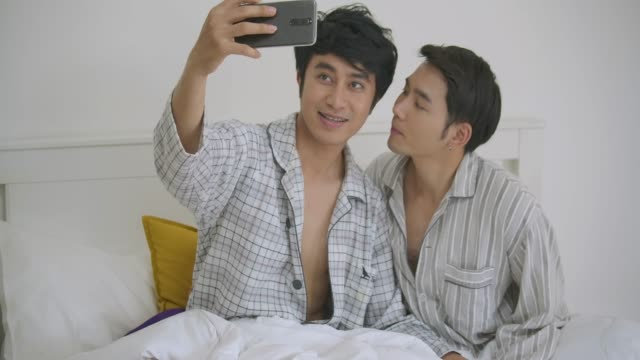 young asian gay couple sitting on bed hug and using phone taking selfie together bedroom at home. lifestyle lgbt couple together indoors concept. - serdeczny filmów i materiałów b-roll