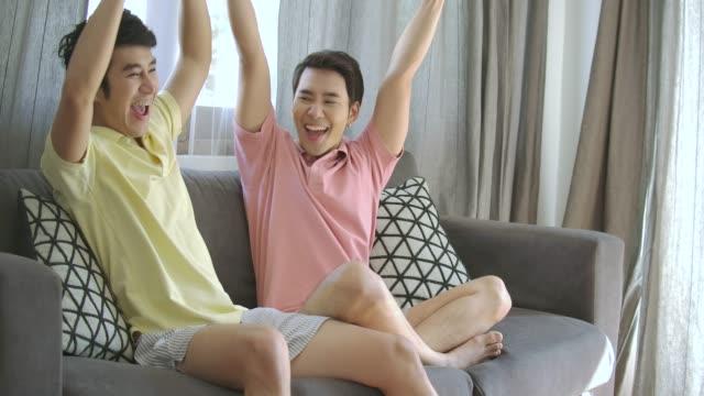 ご自宅のテレビで楽しんで若いアジア同性愛者のカップル見てスポーツ ゲーム。スポーツバーで観戦する人は、自分のチームを応援します。ファンはサッカーの試合を見るし、成功したプレ - 応援点の映像素材/bロール