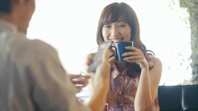 若いアジアの女の子を取るために、ポーズするボーイフレンドは彼女のスマートフォンの写真 - 若者文化点の映像素材/bロール