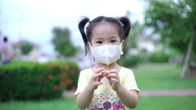 Young Asian girl smiling behind a protective face mask in the park. Concept of new normality.