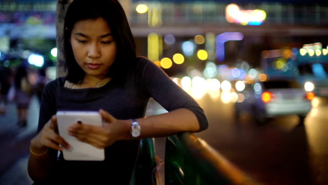 Young Asian Girl using smart phone in night city Young Asian Girl using smart phone in night city bus stop stock videos & royalty-free footage