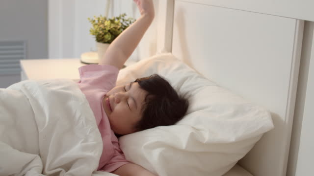 Video Young Asian girl wake up at home. Asia japanese woman child kid relax rest after sleep all night lying on bed, feel comfort and calm in bedroom at home in the morning concept. Slow motion shot.