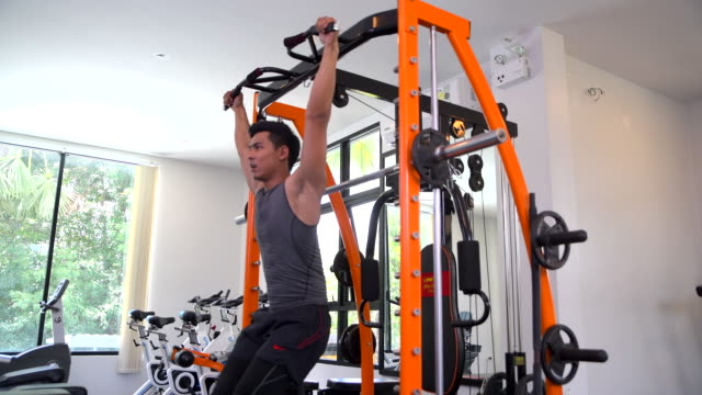young asian handsome man doing exercises in gym - sprzęt do ćwiczeń filmów i materiałów b-roll