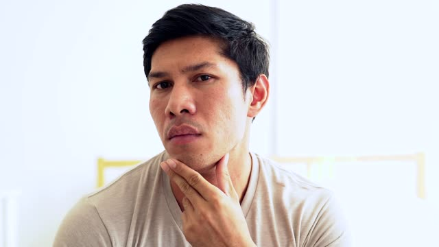 Young Asian handsome man is reflected in the mirror and checks his beard.