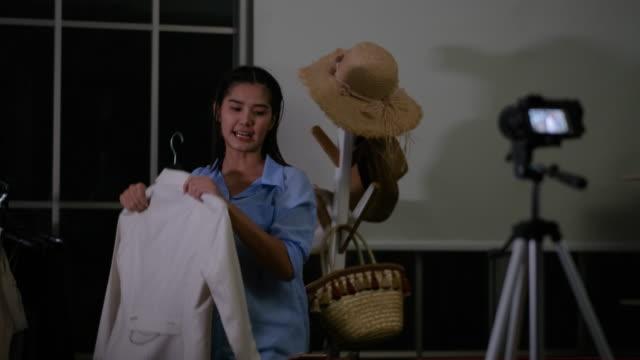 vidéos et rushes de jeune fille asiatique d'influenceur vendent la robe blanche en ligne la nuit et l'action avec l'émotion heureuse - photophone