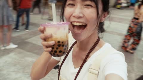 vidéos et rushes de jeune influenceur asiatique avec le thé de boba/bulle tournant autour avec l'appareil-photo dans ximending - hipster personne