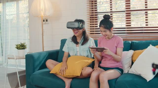 タブレットとバーチャルリアリティを使用して若いアジアのレズビアンのカップルは、自宅のリビングルームでソファを横たえながら一緒にゲームをプレイ。 - ゲーム ヘッドフォン点の映像素材/bロール