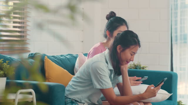 young asian lesbian women couple using mobile phone check social media on internet together while lying sofa in living room. - sud est asiatico video stock e b–roll