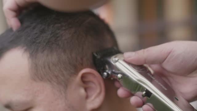 junge asiatische männliche schneiden seine brüder die haare zu hause. - friseur lockdown stock-videos und b-roll-filmmaterial