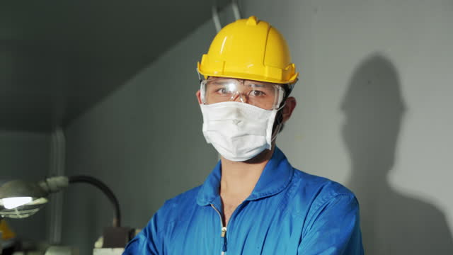 Young Asian male foreman wearing a face mask to prevent COVID 19 infection