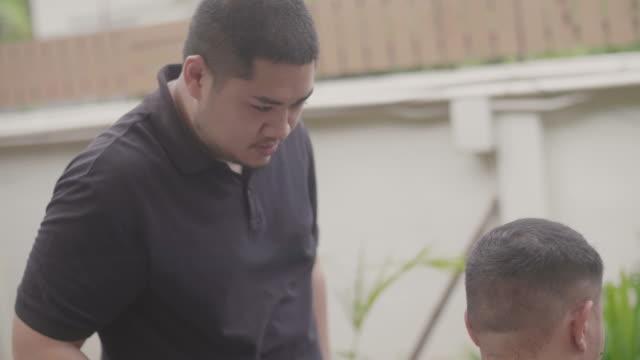 junge asiatische männliche immer haarschnitt von bruder, zu hause. - friseur lockdown stock-videos und b-roll-filmmaterial