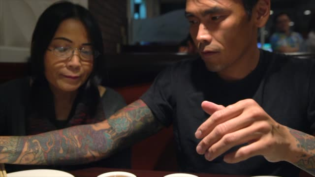 young asian man and old asian woman drinking hot tea together video