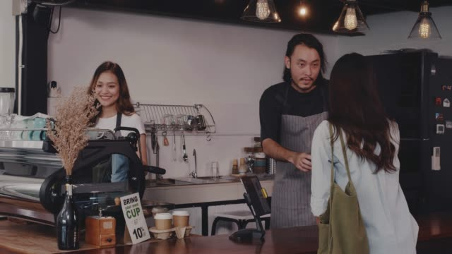 Young Asian man and woman barista wear apron holding hot coffee cup served to customer at bar counter in coffee shop with smile face.Concept of cafe and coffee shop small business.