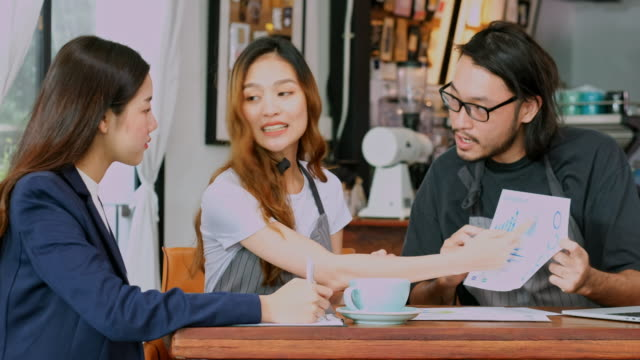 Young asian man and woman, small business explain about financial and business strategy planning to asia business woman in coffee shop cafe