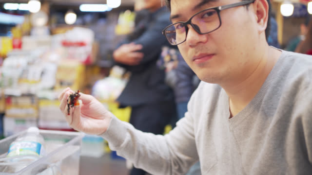 young asian man eating octopus tentacles by chopsticks in delicious at street food market in seoul city, south korea - sashimi video stock e b–roll