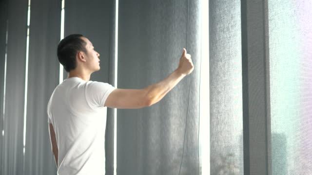 stockvideo's en b-roll-footage met jonge aziatische man probeert te openen van gordijn van het venster op moment van de dag - photography curtains