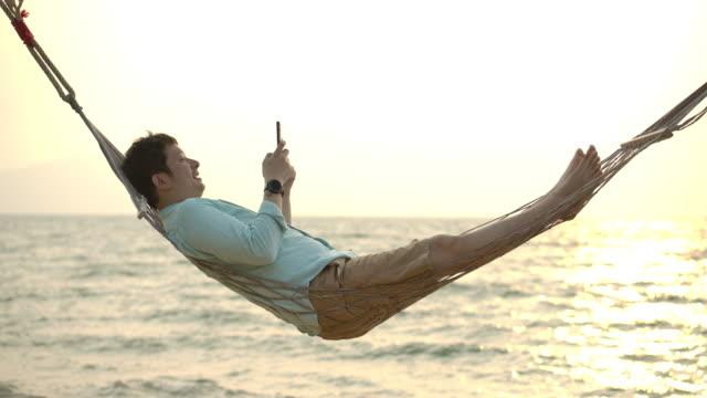 vídeos de stock, filmes e b-roll de jovem asiático olhando para o celular na rede na praia perto do mar ao pôr do sol. - férias na praia