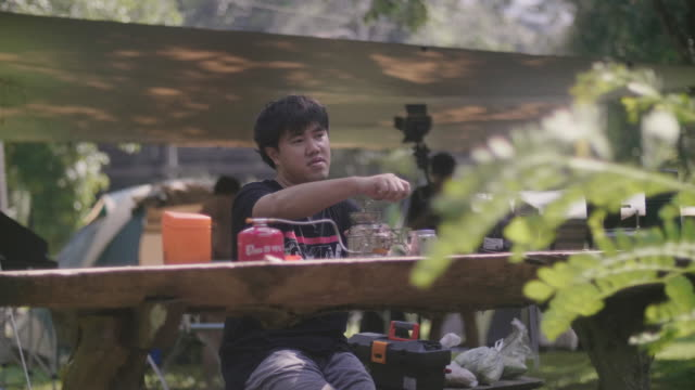 Young Asian man making coffee on a sunny day in the nature.