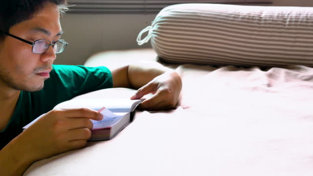 Young Asian man reading book on bed in bedroom