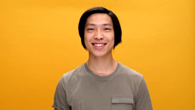Young asian man smiling and showing ok gesture looking at camera isolated over yellow background. video