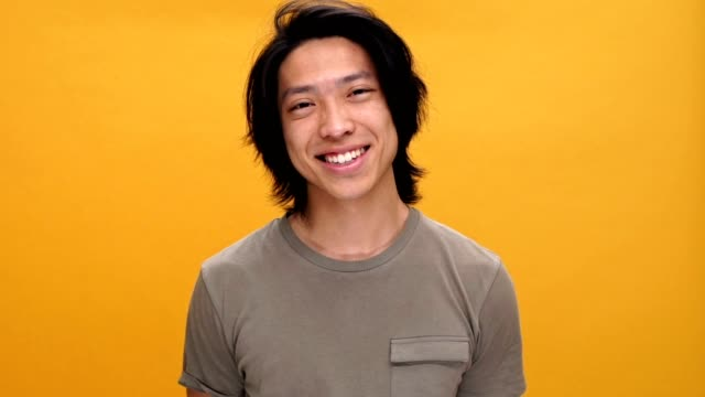 Young asian man smiling and wink isolated over yellow background. video