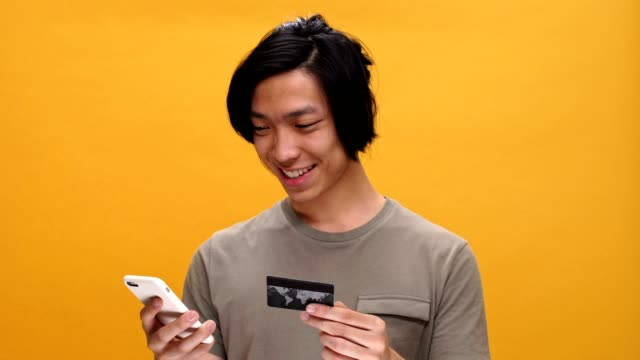 Young asian man smiling holding credit card using phone isolated over yellow background. video