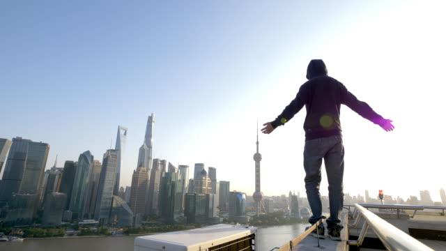 ung asiatisk man står i modern stad - på gränsen bildbanksvideor och videomaterial från bakom kulisserna